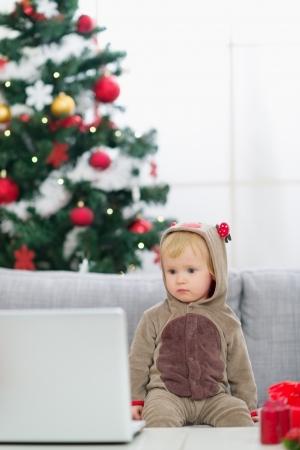 Baby in Christmas deer costume near Christmas tree looking in laptop Stock Photo - 15366325
