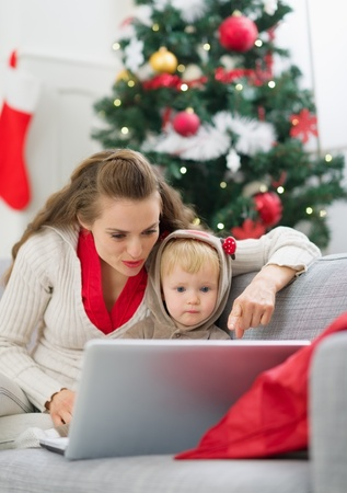 Mother showing baby something in laptop near Christmas tree Stock Photo - 15366313