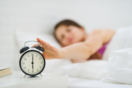 Closeup on woman hand reaching to turn off alarm clock photo
