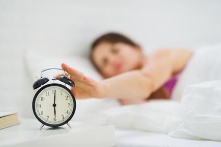 reloj despertador: Primer en la mano mujer alcanza para apagar la alarma del reloj