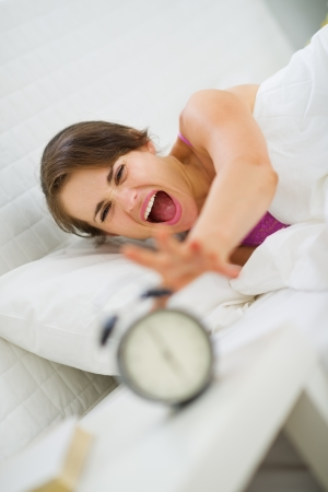 Angry woman stretching to turn off alarm clock Stock Photo - 15411807