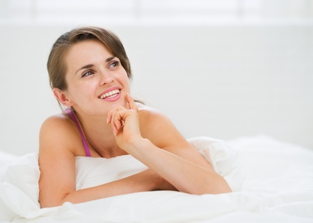 stargaze: Portrait of thoughtful young woman laying on bed