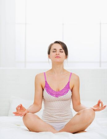 Young woman making yoga on bed Stock Photo - 15411826