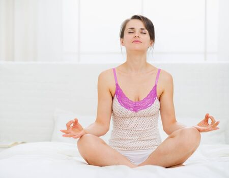 Young woman sitting in yoga pose on bed Stock Photo - 15410900
