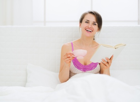 Happy young woman with book and cup in bed Stock Photo - 15410917