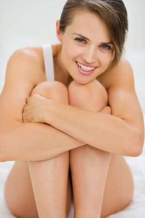 Happy young woman sitting on bed Stock Photo - 15411812