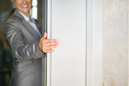 doors open: Closeup on business woman hand holding elevator door Stock Photo
