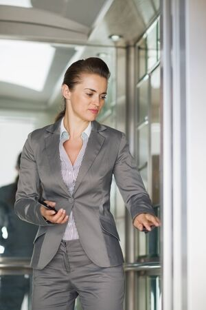 Business woman in elevator pushing button photo