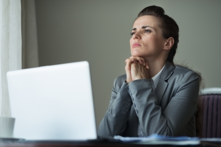 sagacious: Thoughtful business woman working at desk Stock Photo