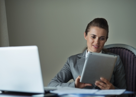 Business woman working with tablet PC in hotel room photo