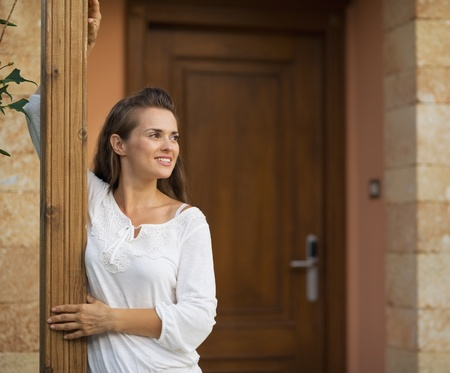 Happy woman standing on doorstep and looking on copy space photo