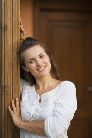 Happy woman standing on doorstep photo