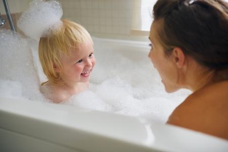aseo personal: Madre y bebé que toma el baño y jugando con espuma