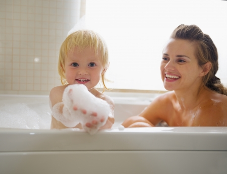 Baby playing with foam while taking bath with mother photo
