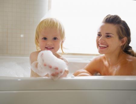 personas banandose: Beb� jugando con espuma mientras toma el ba�o con la madre
