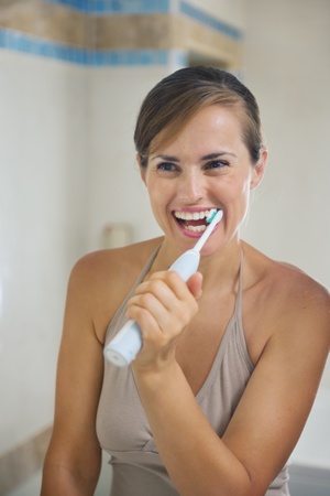 Happy woman brushing teeth with electric toothbrush Stock Photo