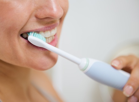 tooth brush: Closeup on woman brushing teeth with electric toothbrush