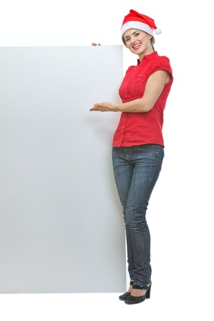 Smiling young woman in Santa hat pointing on blank billboard Stock Photo - 15762159