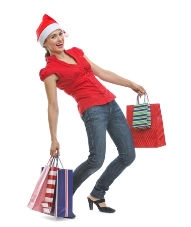 Happy young woman in Santa hat holding heavy shopping bags Stock Photo - 15762152