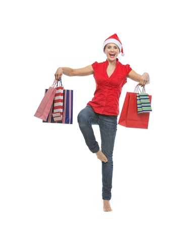 Smiling young woman in Santa hat dancing with shopping bags Stock Photo - 15762134