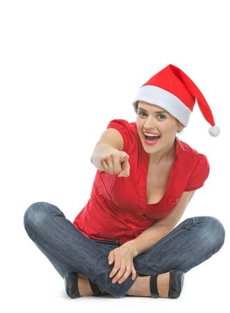 Happy woman in Santa hat sitting on floor and pointing in camera Stock Photo - 15762157