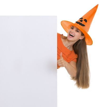 Happy woman in Halloween hat showing blank billboard and thumbs up Stock Photo - 15762210