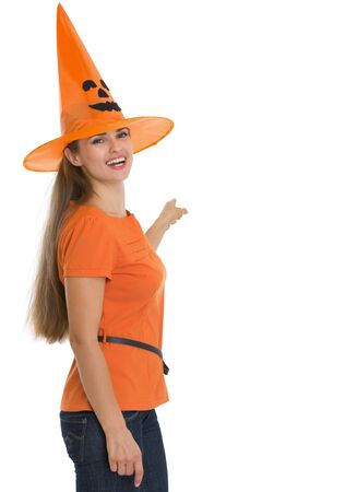 Happy young woman in Halloween hat pointing on back Stock Photo - 15762188