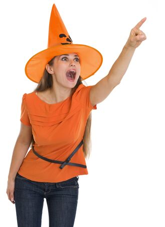 Surprised young woman in Halloween hat pointing on copy space photo