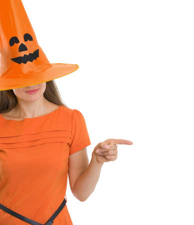 Woman in Halloween hat over eyes pointing on copy space photo