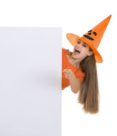 Woman in Halloween hat with blank billboard pointing in camera photo