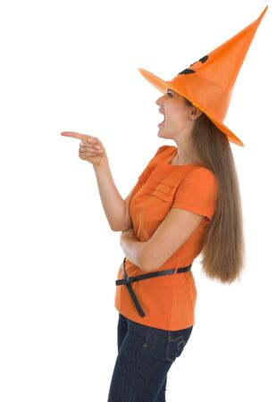 Happy young woman in Halloween hat pointing on copy space photo