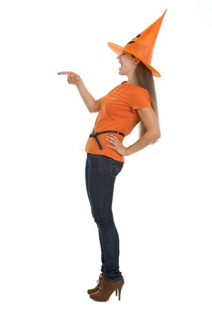 Young woman in Halloween hat pointing on copy space photo