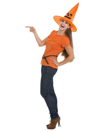 Smiling young woman in Halloween hat pointing on copy space photo