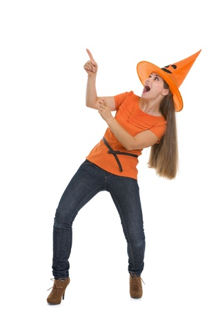 Scared young woman in Halloween hat pointing on copy space photo