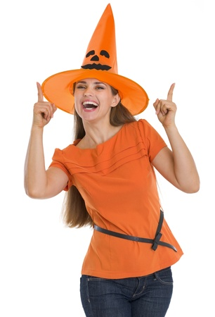 Happy young woman in Halloween hat pointing up Stock Photo - 15787013