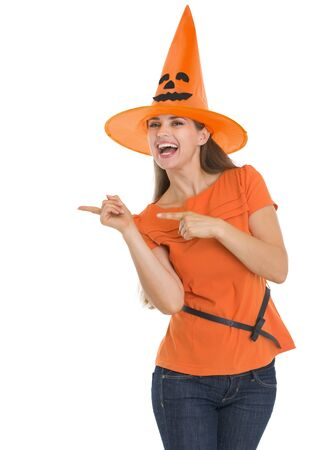 Happy young woman in Halloween hat pointing side photo
