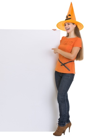 Woman in Halloween hat pointing on blank billboard photo