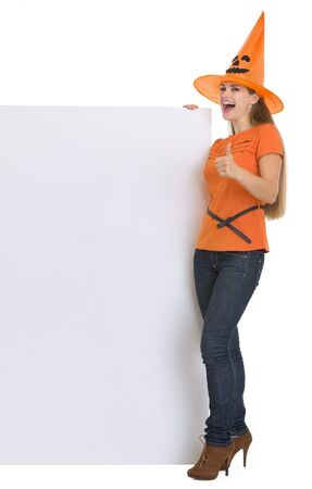 Woman in Halloween hat with blank billboard showing thumbs up Stock Photo - 15786970