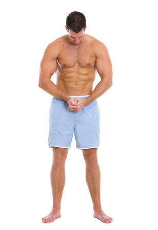 Full length portrait of strong sportsman showing muscles photo