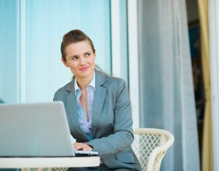 sagacious: Thoughtful business woman working on laptop Stock Photo
