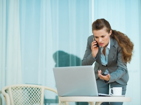 Concerned business woman speaking mobile and looking in laptop photo