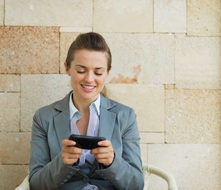 pone: Happy business woman writing text message on cell pone Stock Photo