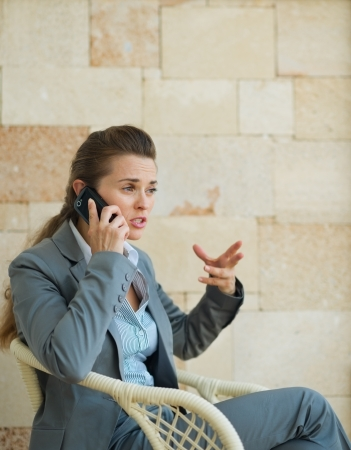disquieted: Concerned business woman speaking mobile phone