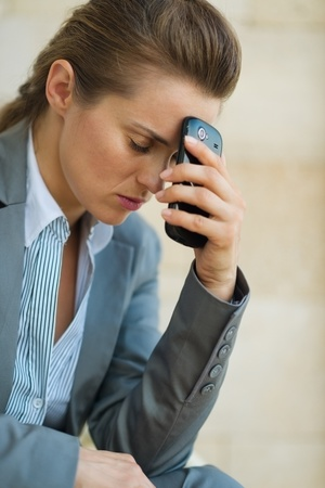 disquieted: Concerned business woman with mobile phone