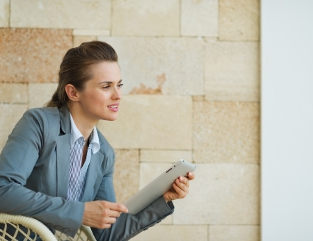 sagacious: Thoughtful business woman holding tablet PC and looking on copy space