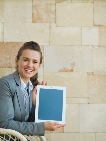 Smiling business woman showing tablet PC photo