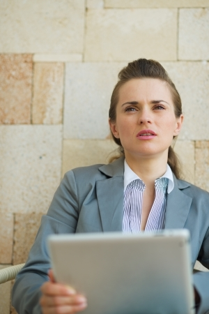 sagacious: Thoughtful business woman holding tablet PC Stock Photo