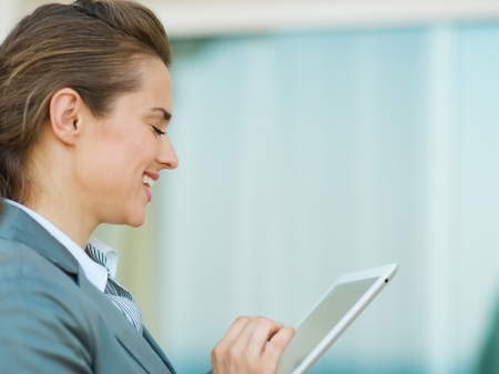 Happy business woman using in tablet PC photo