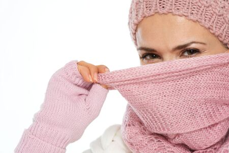 Girl in knit winter clothing closing face with scarf photo