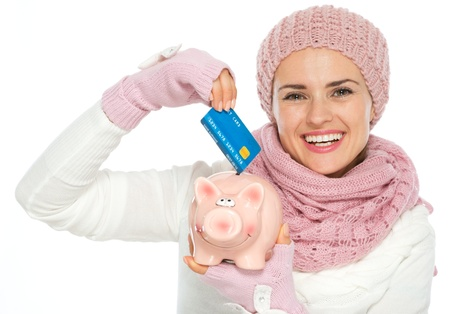 Happy woman in knit winter clothing putting credit card in piggy bank Stock Photo - 15892897